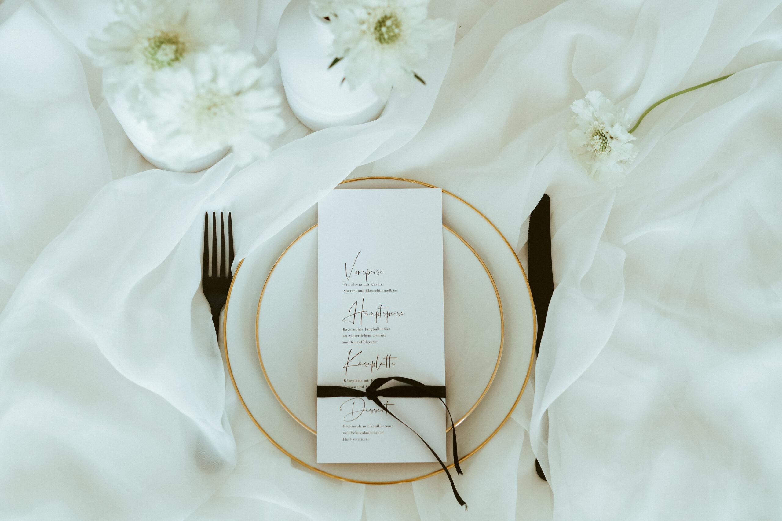 Ein Hochzeitsdesign in Weiß mit schwarzen Akzenten und goldenen Applikationen. Schlicht, airy und edel.